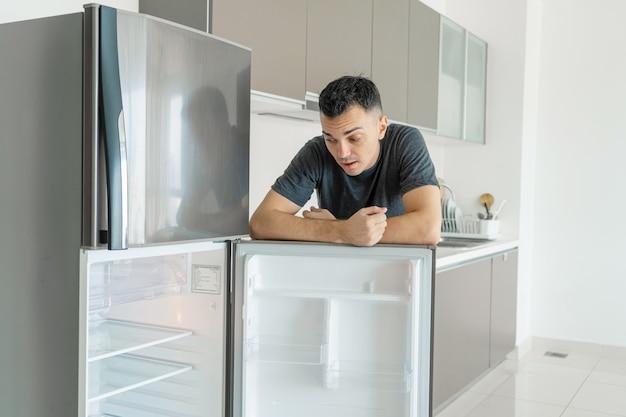 De man is verdrietig bij de lege koelkast zonder eten. advertentie voor bezorgservice voor eten.