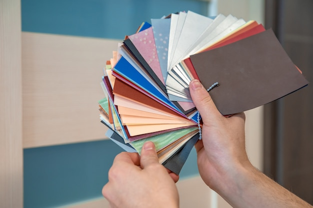 De man kiest het kleurendecor van de nieuwe meubels uit felgekleurde stalen in de meubel- en vloerwinkel