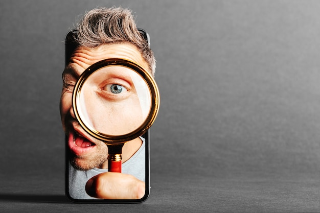De man kijkt door de mobiel in een vergrootglas