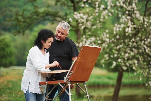 De man kijkt naar zijn vrouw. ouder stel heeft vrije dagen en werkt samen aan de verf in het park