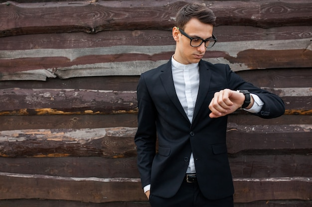De man kijkt op zijn horloge. het boek van de jongenslezing op houten backround wordt geïsoleerd die