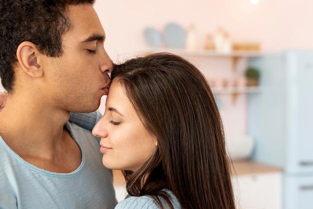De man kussende vrouw van de close-up op het voorhoofd