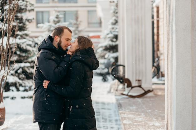 De man kust het meisje zachtjes tegen de achtergrond van de besneeuwde stad