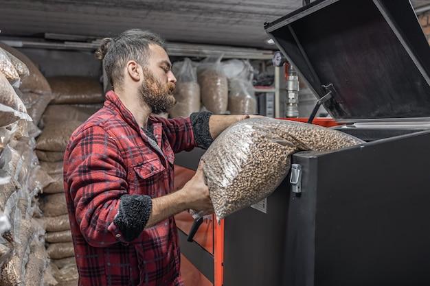De man laadt de pellets in de vastebrandstofketel, werkend met biobrandstoffen, zuinige verwarming.