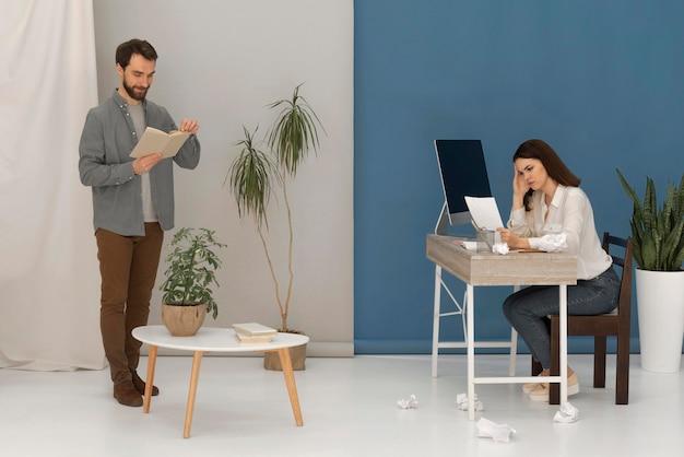 De man leest terwijl de vrouw aan computer werkt