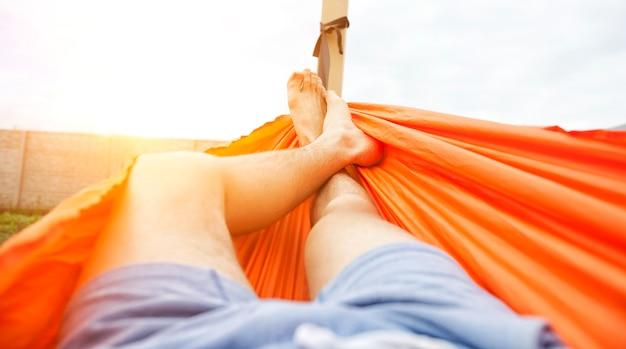 De man ligt te chillen in de hammok