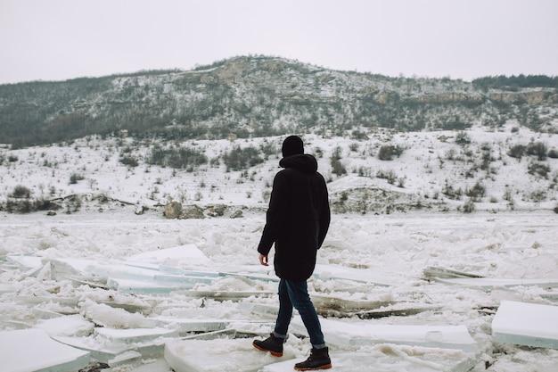 De man loopt alleen in de buurt van de bevroren rivier met haar rug en kijkt naar het prachtige landschap.