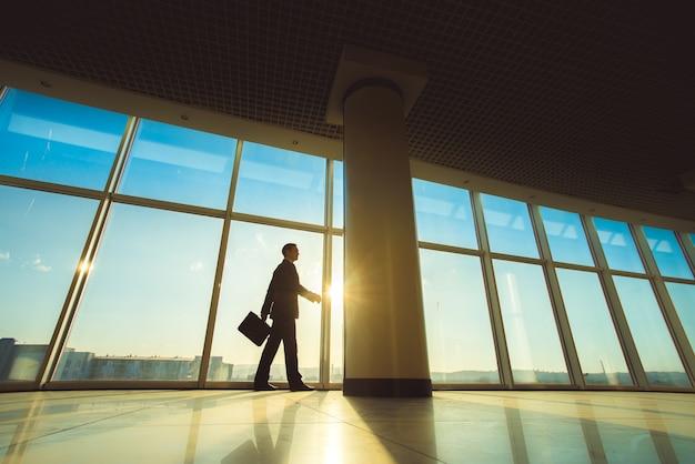De man loopt met een koffer in de kantoorhal