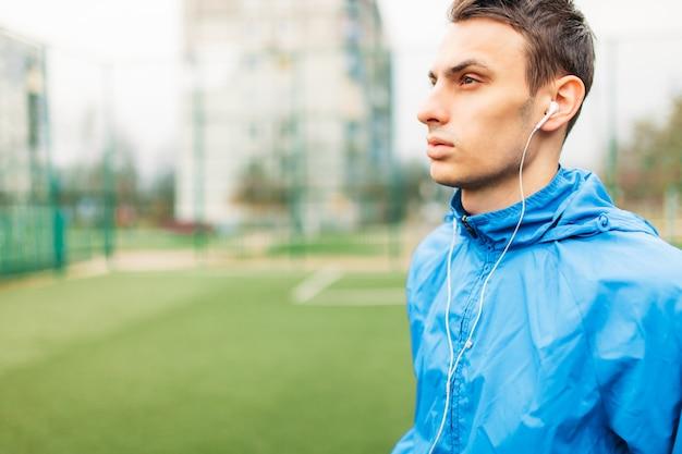 De man luistert naar muziek tijdens een training. een jonge man sport, rent op het voetbalveld. de man werkt in de open lucht.