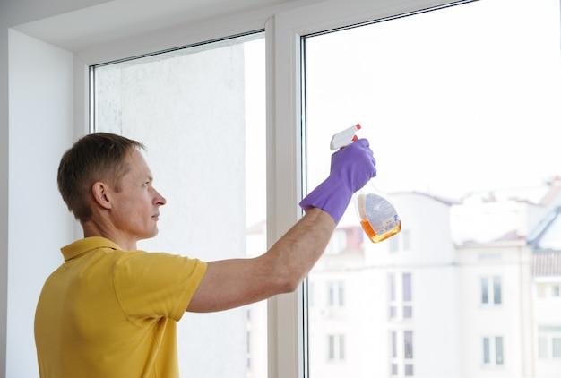 De man maakt de ramen in huis schoon.