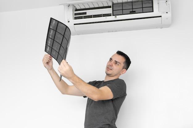 De man maakt het filter van de huisairconditioner schoon van stof. de man snauwde een erg vies airconditioningfilter. en onderzoekt het in zijn handen. verzorging van klimaatapparatuur.