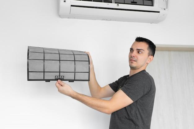 De man maakt het filter van de huisairconditioner schoon van stof. zeer vuil airconditioningsfilter. verzorging van klimaatapparatuur.