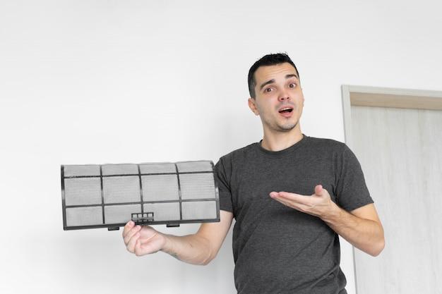 De man maakt het filter van de huisairconditioner schoon van stof.
