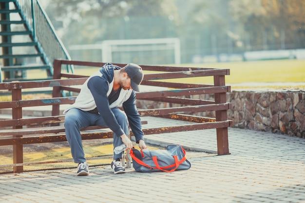 De man maakt zich klaar om te trainen terwijl hij op de bank in het park zit