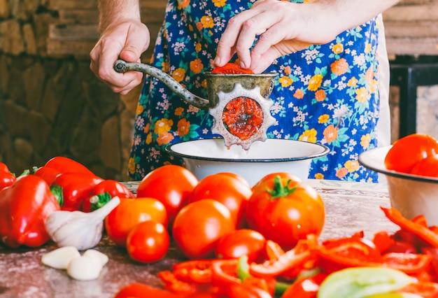 De man maalt stukjes rijpe tomaten in een oude vintage handgehaktmolen.