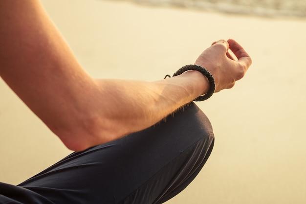 De man mediteert op het strand