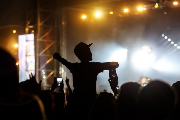 De man met de pet krijgt plezier van het concert, zwart silhouet