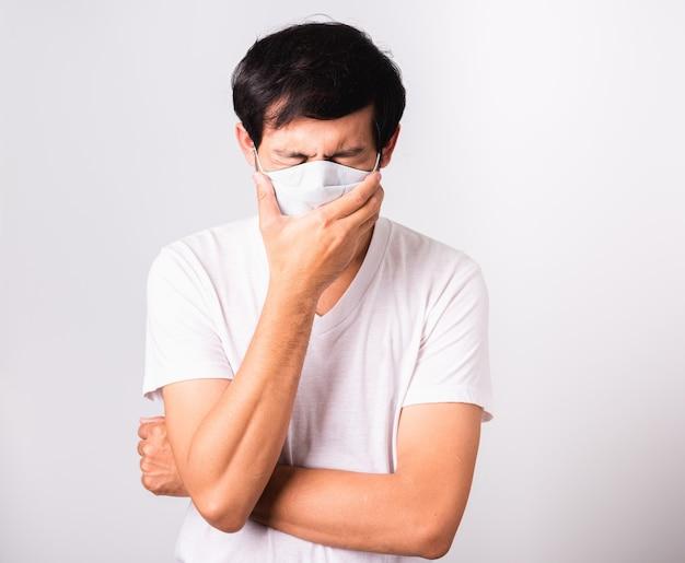 De man met een beschermend gezichtsmasker tegen coronavirus niest hij