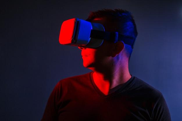 De man met een bril van virtual reality op zwarte geïsoleerde achtergrond.