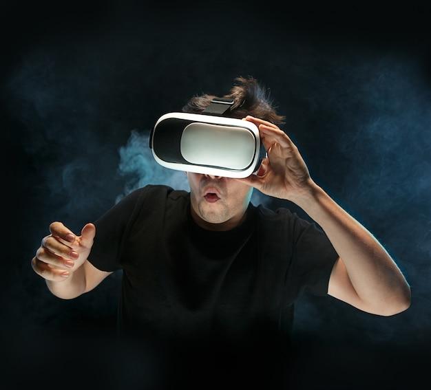 De man met een bril van virtual reality. toekomstig technologieconcept. zwarte studio rokerig