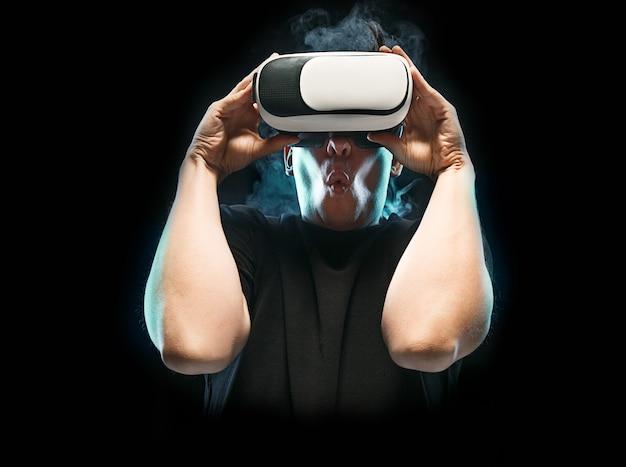 De man met een bril van virtual reality. toekomstig technologieconcept. zwarte studio rokerige achtergrond