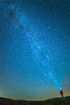 De man met een hoofdzaklamp staat op de achtergrond van de melkweg. nachttijd