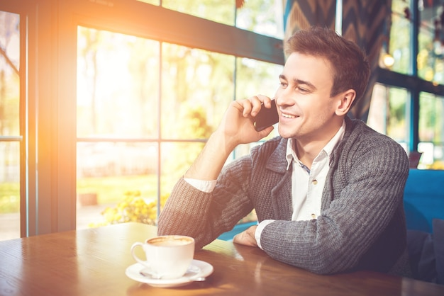 De man met een kopje koffie telefoneert in het restaurant