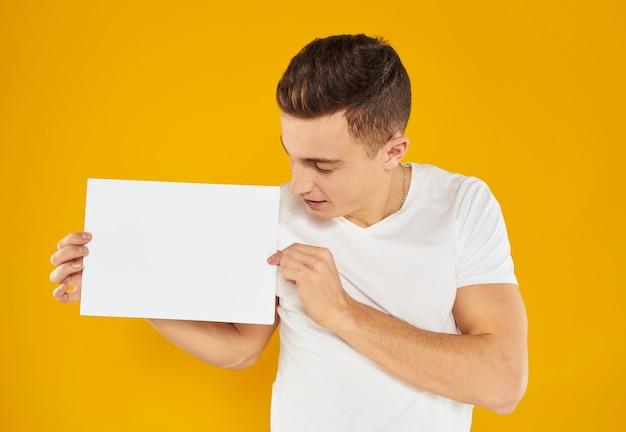 De man met een vel papier op een gele achtergrond hield zijn hoofd schuin naar de bijgesneden zijaanzicht