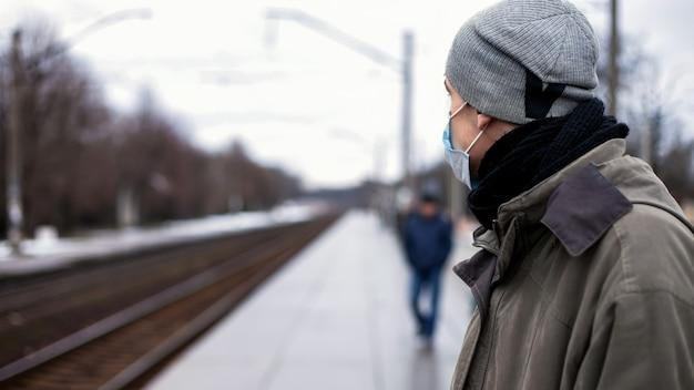 De man met het gasmasker wacht op de trein. concept: verkoudheid, griep, coronavirus