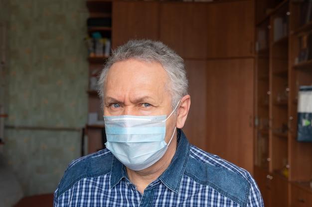 De man met het medische masker zit thuis
