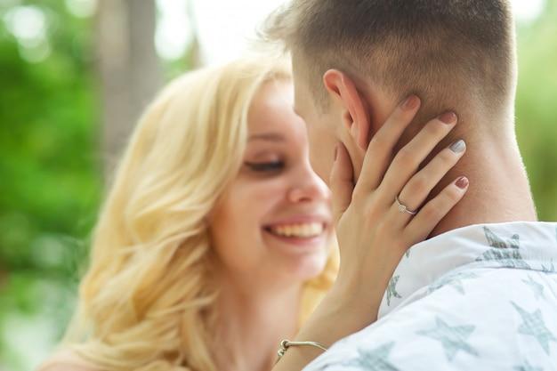 De man met het meisje knuffelt en kust. een romantische date in een dennenbos, liefde paar van een mooi paar