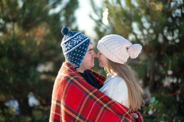 De man met het meisje kuste gewikkeld in een rode geruite plaid