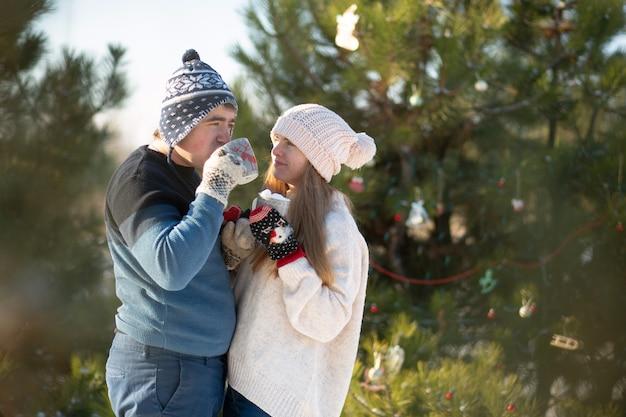 De man met het meisje loopt en kust in het winterbos met een mok warme dranken. een gezellige winterwandeling door het bos met een warm drankje. verliefde paar, wintervakantie
