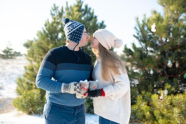 De man met het meisje loopt en kust in het winterbos met een mok warme dranken, een gezellige winterwandeling door het bos met een warme drank, verliefde paar, wintervakantie