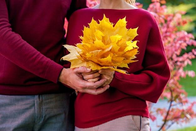 De man met het meisje met een kleurrijk boeket herfstbladeren. detailopname.