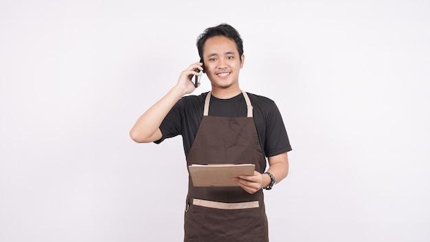 De man met het schort staat op een witte achtergrond geïsoleerd op de menulijst met telefoon