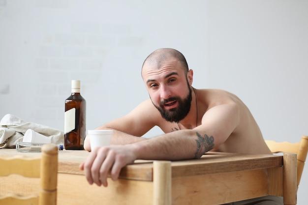 De man met het verstand verduisterd door alcohol of drugs kijkt in de camera.