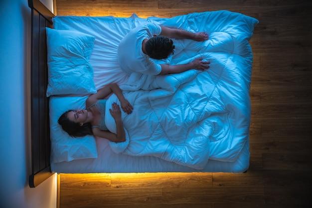 De man met slapeloosheid zit in de buurt van een slapende vrouw op een bed. uitzicht van boven