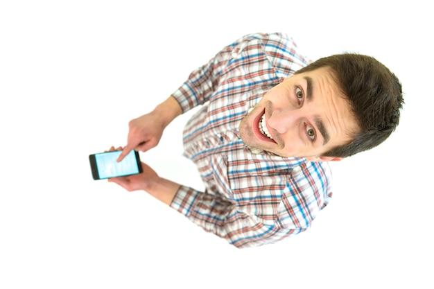 De man met smartphone kijkt naar de camera. uitzicht van boven