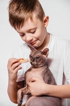 De man met veel plezier eet een stuk pizza en plaagt een kale kat op een witte muur