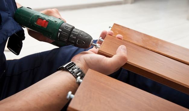 De man monteert thuis houten meubels