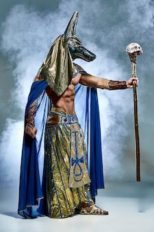 De man naar het beeld van de oude egyptische farao met een masker op zijn gezicht