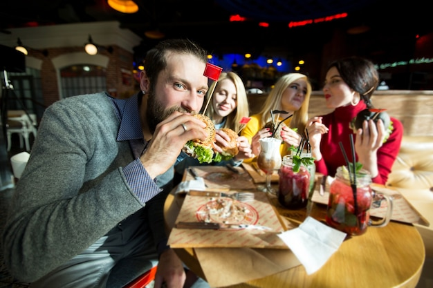 De man neemt een hap van zijn hamburger en kijkt naar de camera. mooie vrouwen lachen en communiceren.