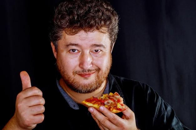 De man neemt smakelijke handen en neemt een heerlijk stukje pizza.