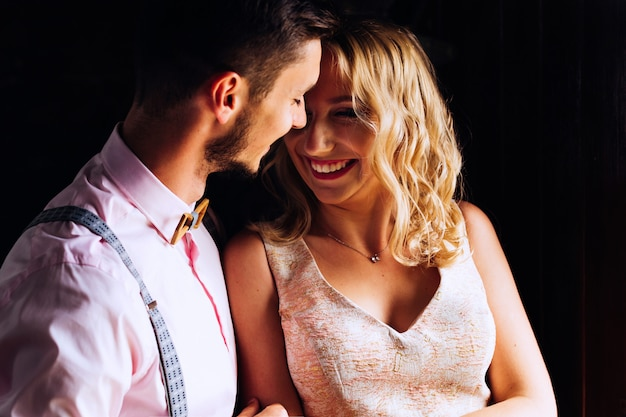 De man omhelst zachtjes zijn vriendin, die oprecht lacht om de donkere achtergrond