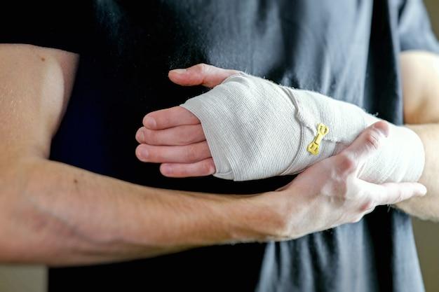 De man ondersteunt de gewonde hand eerstelijnszorg de hand wordt stevig vastgemaakt met een elastisch verband