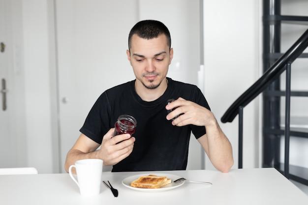 De man ontbijt met toast met jam.