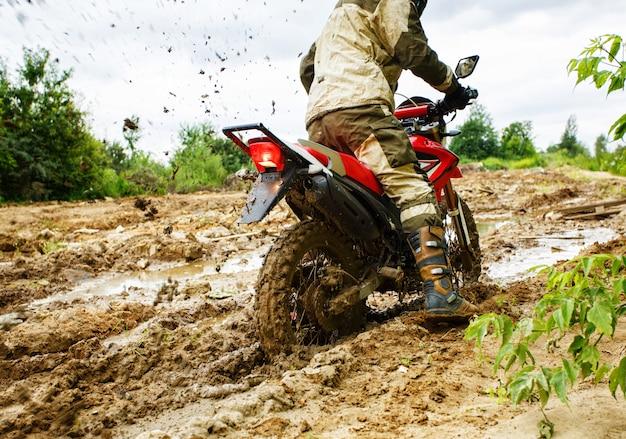 De man op een motorfiets rijdt door de modder