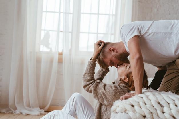 De man op het bed kust een vrouw die op de vloer zit