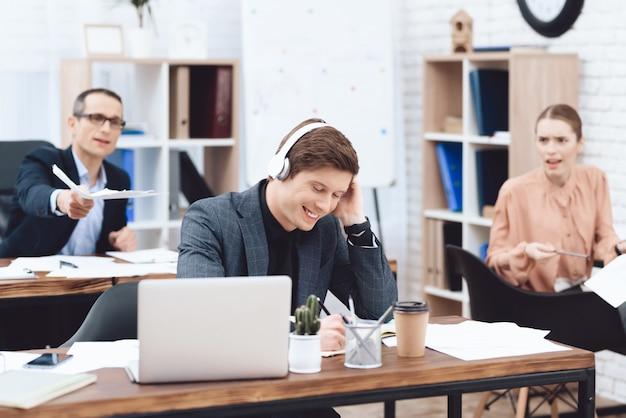 De man op het werk luistert naar muziek en wil niet werken